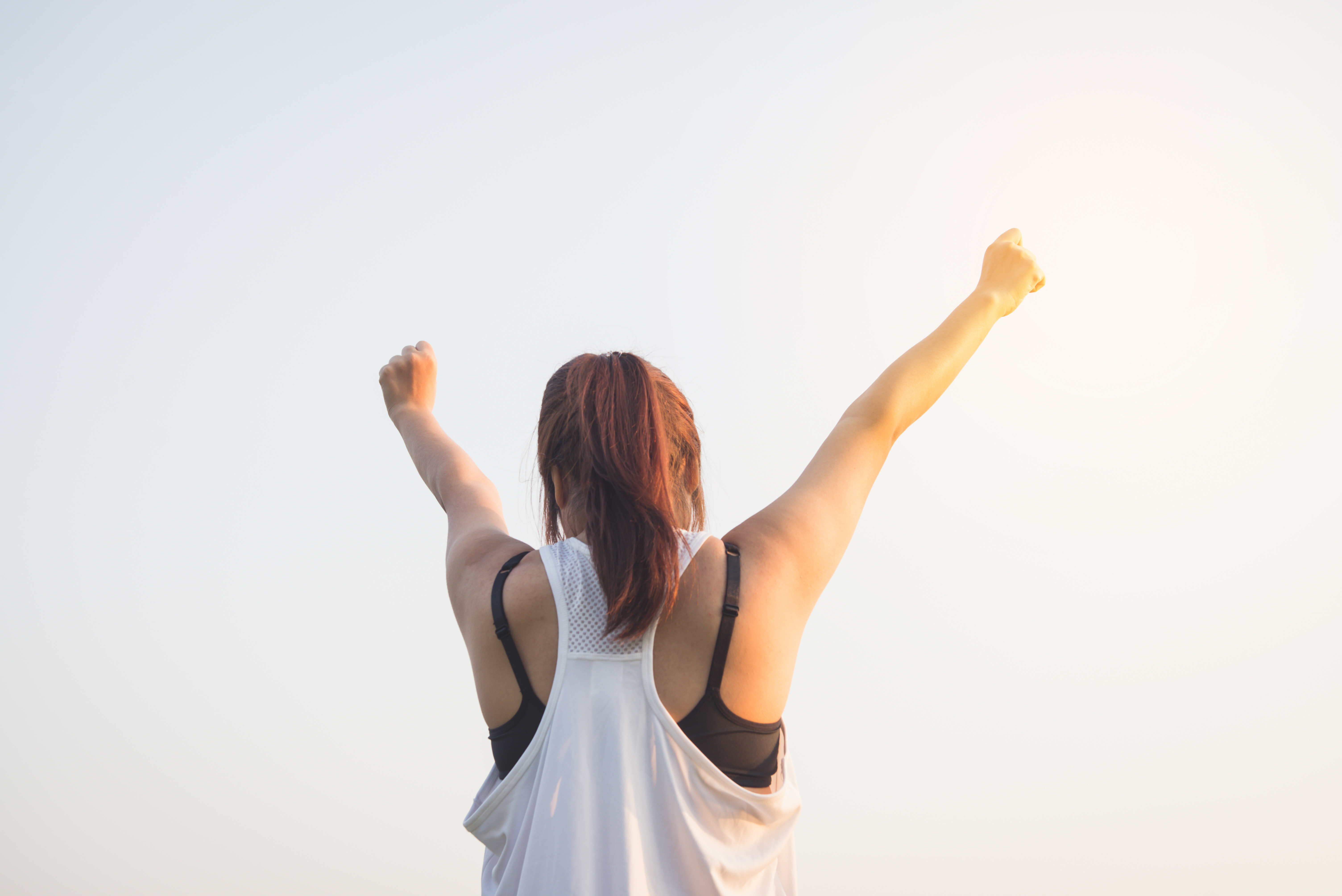 Happy successful sportswoman raising arms to the sky on golden b